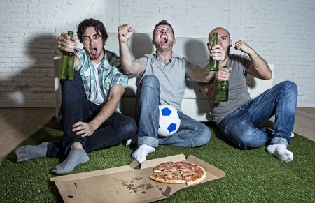 carpet grass: group of friends fanatic football fans watching soccer game on television celebrating goal on grass carpet emulating stadium pitch screaming excited and ecstatic crazy happy with beer and pizza