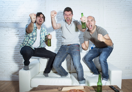 fanatics: group of friends fanatic football fans watching soccer game on television celebrating goal jumping on couch screaming excited and ecstatic and crazy happy with beer bottles and pizza