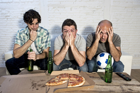 fanatic: group of friends fanatic football fans watching soccer game on television with beer bottles and pizza suffering stress and crazy nervous on couch concentrated and focused Stock Photo