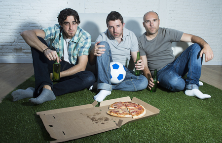 fanatic: group of friends fanatic football fans watching soccer game on television with beers and pizza on grass carpet emulating stadium pitch looking nervous and stressed very focused on the match Stock Photo
