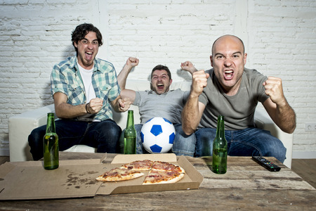 fanatics: group of friends fanatic football fans watching soccer game on television celebrating goal on couch screaming excited and ecstatic in crazy happy face expression with beer and pizza
