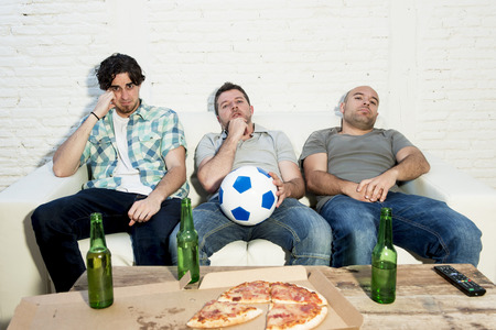 dejected: group of friends fanatic football fans watching soccer game on television with beer bottles and pizza suffering stress and crazy nervous on couch sad and dejected as if their team is loosing