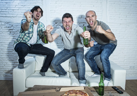 screaming: group of friends fanatic football fans watching soccer game on television celebrating goal jumping on couch screaming excited and ecstatic and crazy happy with beer bottles and pizza