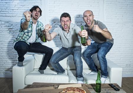 grupo de amigos fanáticos aficionados al fútbol viendo fútbol en televisión celebrando saltar meta en el sofá gritando emocionados y éxtasis y loco feliz con botellas de cerveza y la pizza