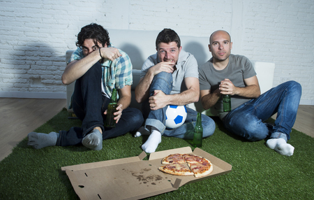 fanatic: group of friends fanatic football fans watching soccer game on television with beers and pizza on grass carpet emulating stadium pitch looking nervous and anxious suffering stress