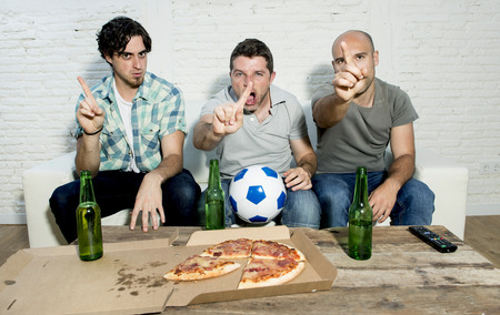 fanatic: group of friends fanatic football fans watching soccer game on television with beer bottles and pizza suffering stress and crazy nervous on couch  complaining gesturing no with finger