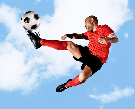 plasticity: young football player kick ball in skillful volley jumping on the air in dynamic pose wearing red jersey and socks isolated on blue sky background shot in sport advertising style