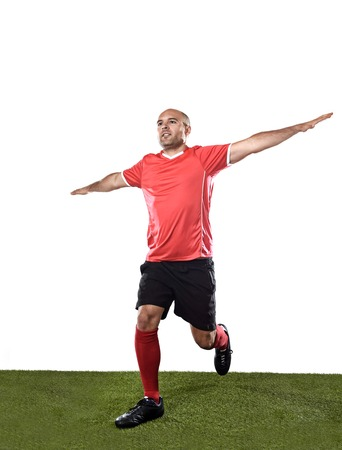 winning pitch: young happy and excited football player in red jersey running on grass pitch and celebrating scoring goal doing flying airplane arms sign isolated on white background