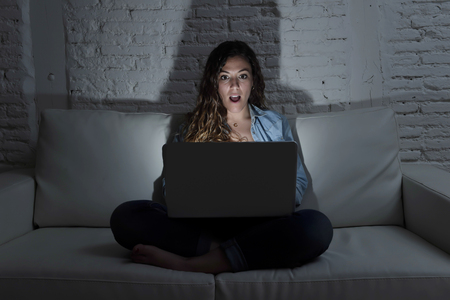 overuse: young attractive woman at home sitting at living room sofa couch using laptop computer in dark evening light with intense face expression in internet and network addiction concept at night