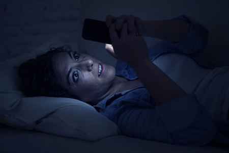 cell phone addiction: young beautiful woman lying on home sofa couch using mobile phone texting or enjoying app fully concentrated and focused at night in internet and social network addiction Stock Photo