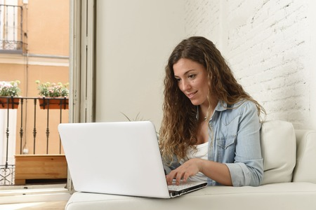 spanish woman: young attractive spanish woman in denim casual clothes using laptop computer sitting relaxed working on home sofa couch at living room enjoying happy and calm in domestic internet concept