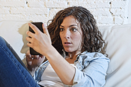 overuse: young hispanic woman holding mobile phone looking in crazy eyes social network addict face expression at home couch in telephone addiction and internet overuse concept Stock Photo