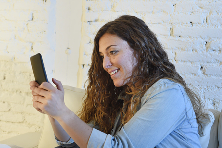 spanish home: young attractive spanish woman in denim casual clothes using mobile phone app or texting on home sofa couch at living room enjoying happy and calm in internet social network and communication concept Stock Photo