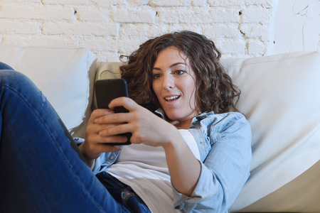 spanish woman: young attractive spanish woman in denim casual clothes using mobile phone app or texting on home sofa couch at living room enjoying happy and calm in internet social network and communication concept Stock Photo
