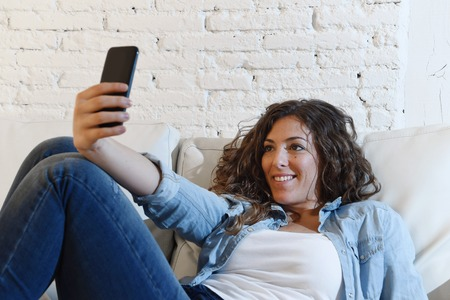 self   portrait: young attractive hispanic woman lying on home sofa couch alone taking selfie photo with mobile phone having fun enjoying and smiling happy shooting self portrait