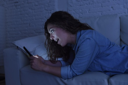 cell phone addiction: young beautiful woman lying on home sofa couch using mobile phone texting or enjoying app happy and excited at night in internet and social network addiction