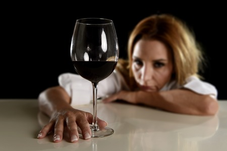 drunk girl: drunk blond woman alone in wasted depressed expression looking thoughtful and sad holding red wine glass isolated on black background in alcohol abuse and alcoholic housewife concept Stock Photo