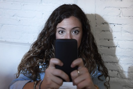 cell phone addiction: young hispanic woman holding mobile phone looking in crazy eyes social network addict face expression at home couch in telephone addiction and internet overuse concept Stock Photo