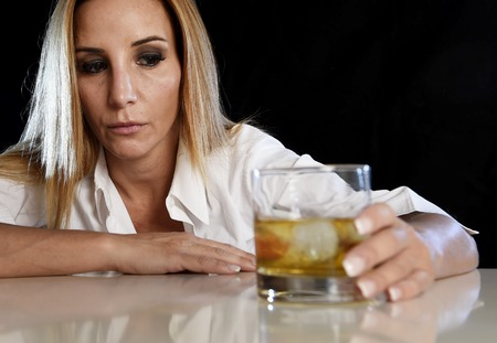 bad girl: drunk woman alone in wasted and depressed face expression holding and looking thoughtful to scotch whiskey glass isolated on black background in alcohol abuse and alcoholic housewife concept Stock Photo