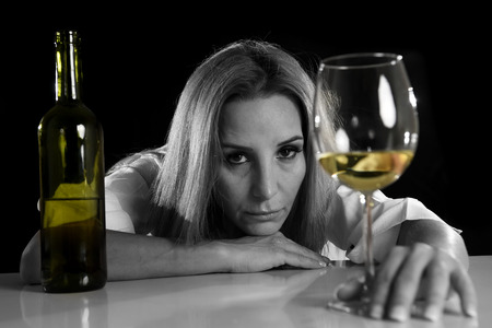 drunk girl: drunk blond woman alone in wasted depressed face expression looking thoughtful holding white wine glass isolated on black background in alcohol abuse and alcoholic housewife concept
