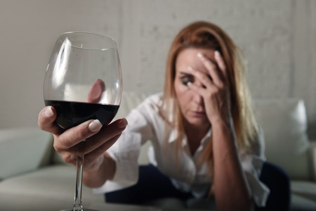 completely: blond sad and wasted alcoholic woman sitting at home sofa couch drinking red wine holding glass completely drunk looking depressed lonely and suffering hangover in alcoholism and alcohol abuse