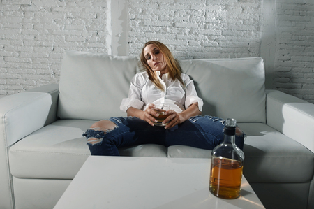 blond sad and wasted alcoholic drunk woman sitting at home sofa couch drinking scotch whiskey holding glass depressed lonely and suffering hangover in alcoholism and alcohol abuse concept Stock Photo