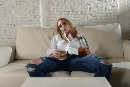 blond sad and wasted alcoholic drunk woman sitting at home sofa couch drinking scotch whiskey holding glass and bottle lonely and suffering hangover in alcoholism and alcohol abuse
