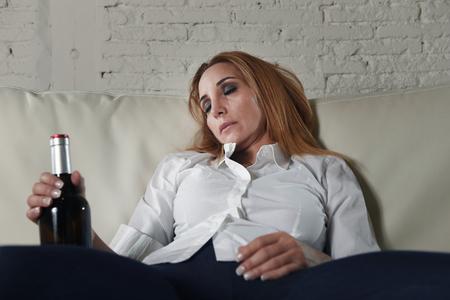 rubia triste y la pérdida de la mujer alcohólica se sienta en el sofá en casa sofá bebiendo vino rojo que sostiene la botella borracha durmiendo la resaca que parece presionado solitario y el sufrimiento en el alcoholismo y el abuso del alcohol