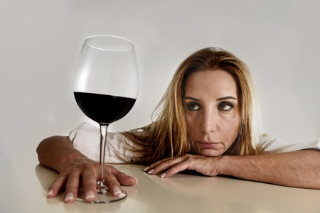 liquor girl: caucasian blond wasted and depressed alcoholic woman drinking red wine glass looking desperate and sad isolated on white in alcohol abuse and addiction and housewife alcoholism problem