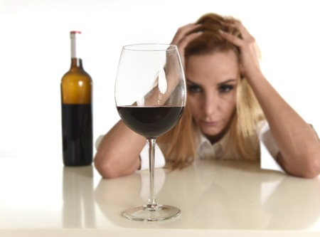 drinking problem: caucasian blond wasted and depressed alcoholic woman drinking red wine glass looking desperate and sad isolated on white in alcohol abuse and addiction and housewife alcoholism problem
