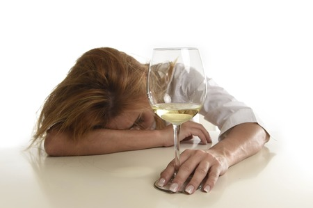 drinking problem: caucasian blond wasted and depressed alcoholic woman drinking white wine glass looking desperate and sad isolated on white in alcohol abuse and addiction and housewife alcoholism problem Stock Photo