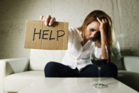 drunk alcoholic blond woman drinking whiskey glass asking for help holding message board depressed wasted and sad at home couch in alcohol abuse and housewife alcoholism