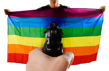 intolerance: intolerance and violent representation of terrorist attack with close up hand holding gun pointing on proud gay man spreading wide big pride homosexual flag