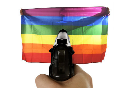 anti racist: intolerance and violent representation of terrorist attack with close up hand holding gun pointing on proud gay man spreading wide big pride homosexual flag