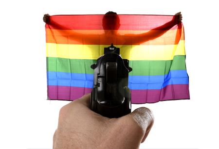 intolerancia: la intolerancia y la representaci�n violenta de un ataque terrorista con cierre encima de la mano que sostiene el arma que se�ala en el hombre gay orgulloso amplia propagaci�n gran orgullo la bandera homosexual Foto de archivo
