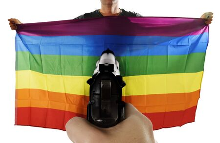 intolerancia: intolerance and violent representation of terrorist attack with close up hand holding gun pointing on proud gay man spreading wide big pride homosexual flag
