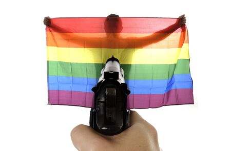 anti fascist: intolerance and violent representation of terrorist attack with close up hand holding gun pointing on proud gay man spreading wide big pride homosexual flag