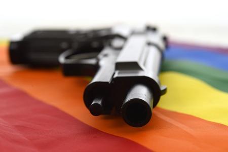 intolerancia: Todav�a vida con cierre encima de la pistola apoyada en la bandera desfile gay que representa la discriminaci�n sexual y la intolerancia y el ataque a los derechos humanos y la libertad sexual