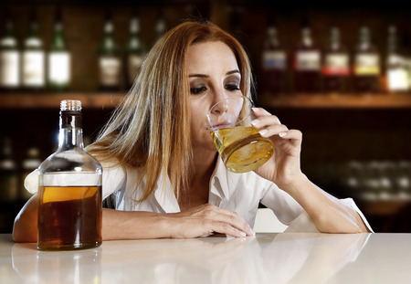 drunk woman alone in wasted and depressed face expression drinking scotch whiskey glass sitting at bar or pub in alcohol abuse and alcoholic housewife concept