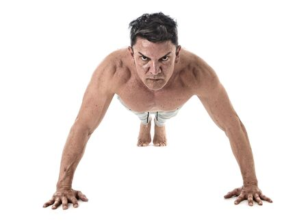 40 45: 40 to 45 years old attractive fit man doing push up workout training hard  fitness routine with strong muscular body isolated on white background in health sport and bodybuilding concept