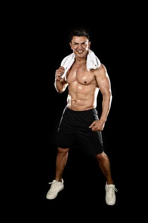 hombre atractivo deporte feliz con cuerpo de culturista fuerte en forma posando gimnasio corporativo sonriendo con toalla en el cuello sudoración húmeda aislado sobre fondo negro en concepto de dieta y salud de belleza de fitness Foto de archivo