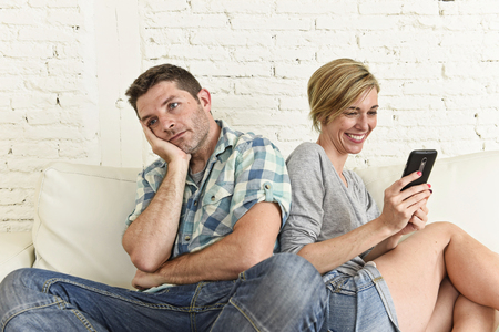 ignoring: young attractive couple at home living room couch with happy woman using internet app on mobile phone ignoring bored and sad man in social network and smart phone addiction concept Stock Photo