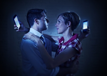 overuse: couple of lovers hugging each other in love but in fact looking at the mobile phone over the shoulder in relationship communication problem and internet social network addiction concept