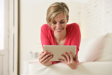 young beautiful and happy 30s woman smiling enjoying using digital tablet pad at home living room couch in domestic technology and internet social network concept Stock Photo