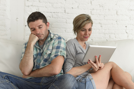 ignoring: young attractive couple husband and wife at home living room couch with happy woman using internet app on digital tablet pad ignoring bored and sad man in social network addiction concept