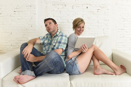 overuse: young attractive couple at home living room couch with happy woman using internet app on digital tablet pad ignoring bored and sad man in social network and technology overuse and addiction concept Stock Photo