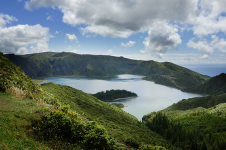 holiday destinations: amazing landscape view of crater volcano lake in Sao Miguel island of Azores in Portugal with green mountains and beautiful turquoise color water reflecting sky in holiday destinations and travel concept