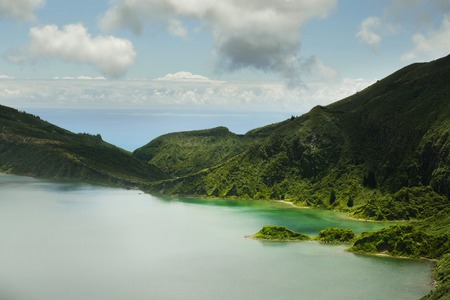 amazing landscape view of crater volcano lake in Sao Miguel island of Azores in Portugal with green mountains and beautiful turquoise color water reflecting sky in holiday destinations and travel concept