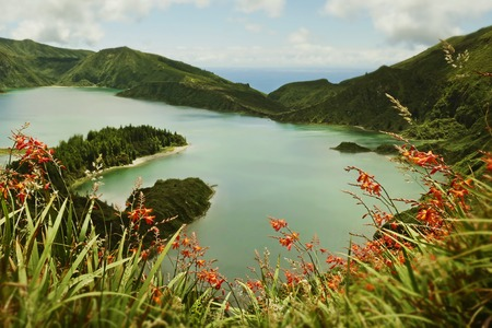 holiday destinations: amazing landscape view of crater volcano lake in Sao Miguel island of Azores in Portugal with flowers and beautiful turquoise color water reflecting sky in holiday destinations and travel concept Stock Photo