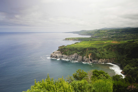 amazing landscape view of Sao Miguel island coast in Azores Portugal from top tourist viewpoint in cloudy sky and beautiful soft light shining on the atlantic ocean in travel destination concept Stock Photo